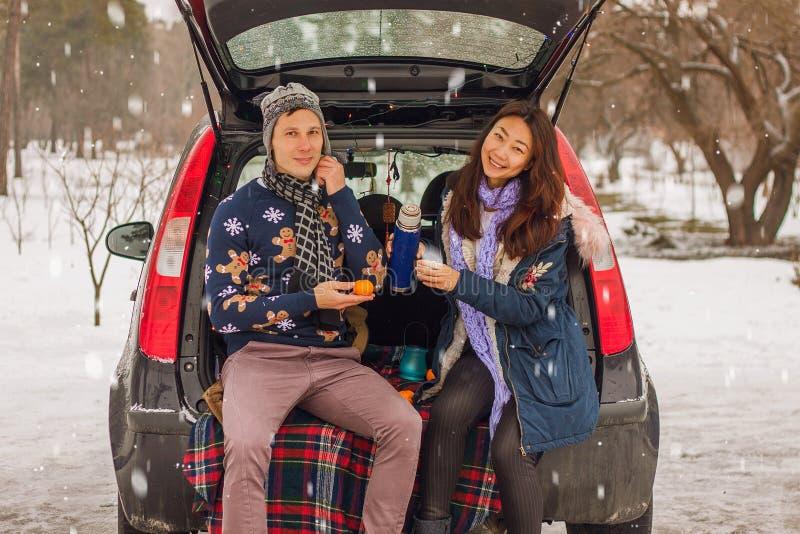 Pares internacionais bonitos que relaxam na natureza no inverno Reunião romântica de um par no amor na neve Os pares novos sentam imagens de stock royalty free