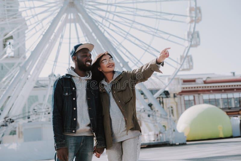 Pares internacionales jovenes alegres que caminan en la ciudad imágenes de archivo libres de regalías