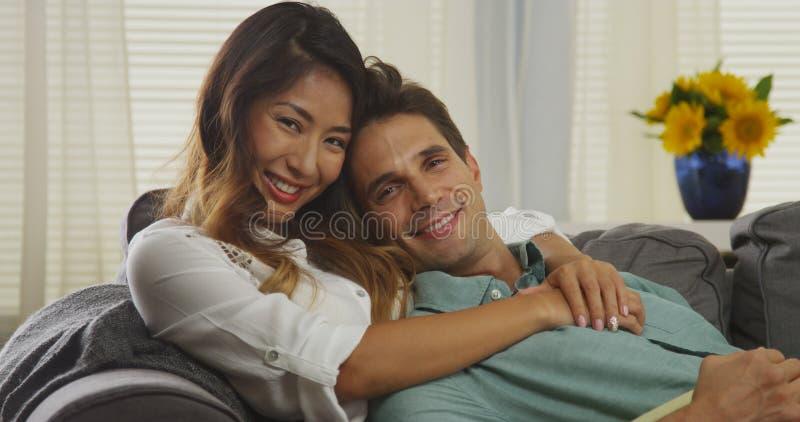 Pares interraciales atractivos que se sientan en el sofá imagenes de archivo
