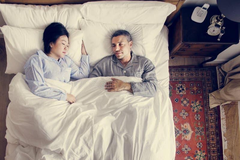 Pares interraciales que duermen junto en la cama imagenes de archivo