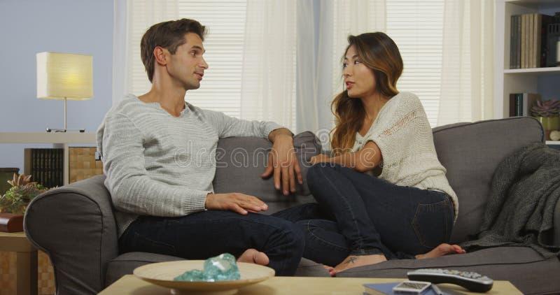 Pares interraciales que hablan en el sofá foto de archivo