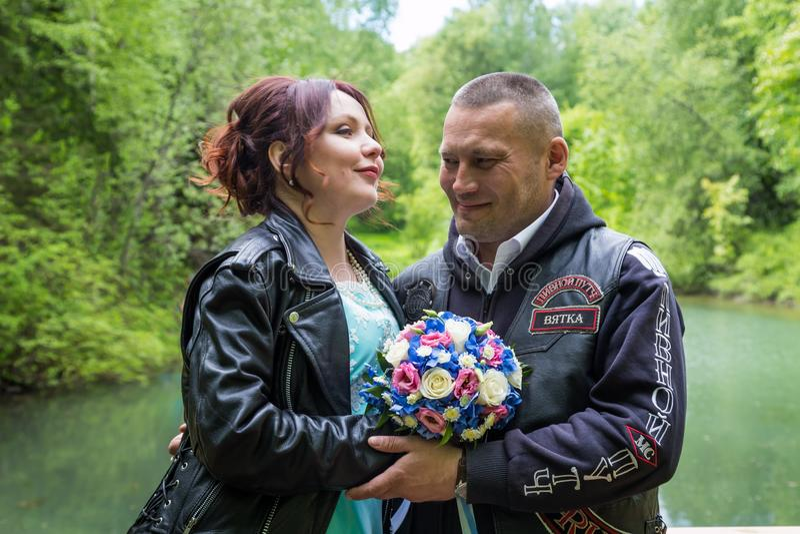 Pares inusuales de la boda incluyendo novia y novio en la chaqueta de cuero del eje de balancín en el parque verde fotografía de archivo