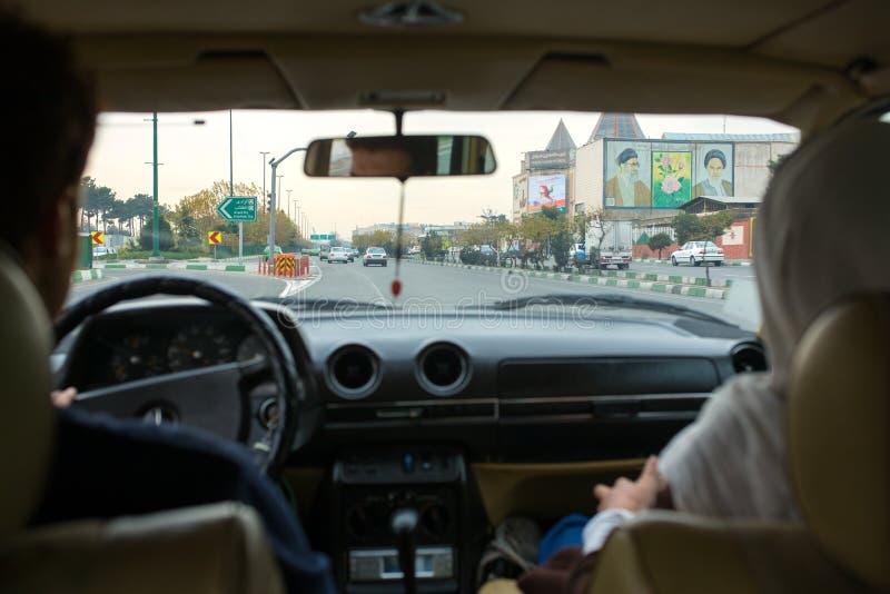 Pares iranianos que conduzem seu carro nas ruas de Tehran que passam por retratos dos líderes supremos da república islâmica de I foto de stock royalty free