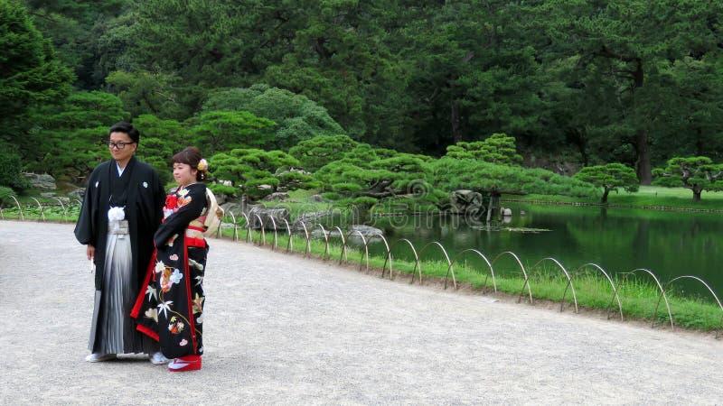 Pares japoneses de la boda en Ritsurin Koen Garden Takamatsu Japan fotografía de archivo