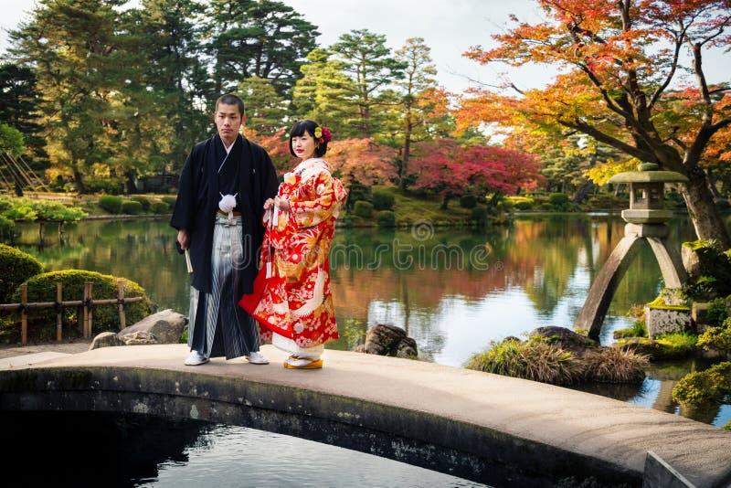 Pares japoneses do casamento no suporte tradicional do quimono em uma ponte no parque de Kenrokuen, cidade de Kanazawa, Japão imagem de stock royalty free
