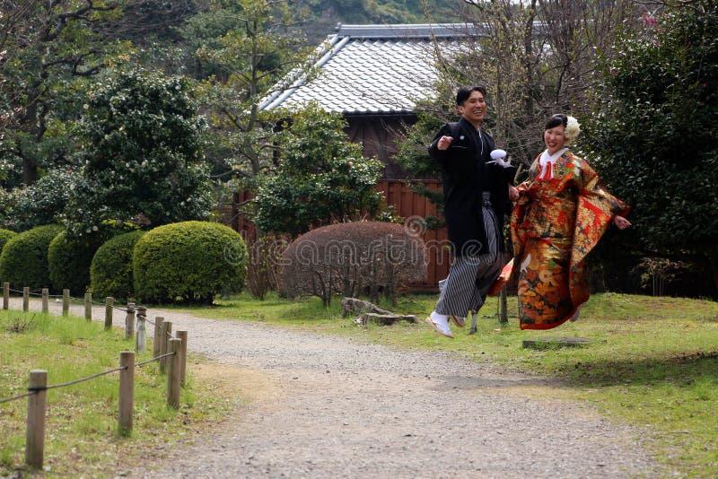 Pares japoneses novos tradicionais que saltam para a alegria no parque imagens de stock royalty free