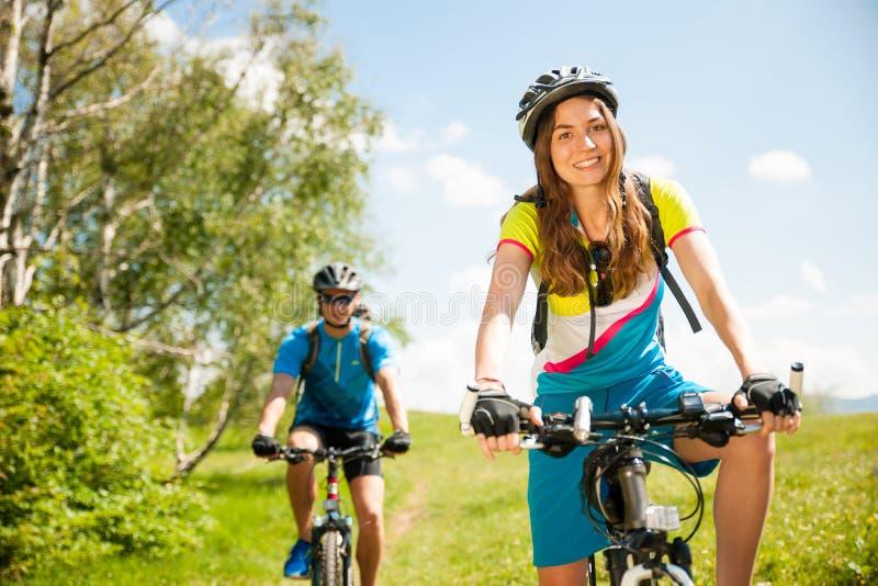 Pares jovenes ACTIVOS biking en un camino forestal en montaña en un spr foto de archivo libre de regalías