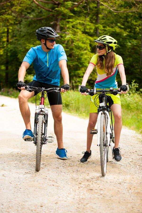 Pares jovenes ACTIVOS biking en un camino forestal en montaña en un spr fotos de archivo libres de regalías
