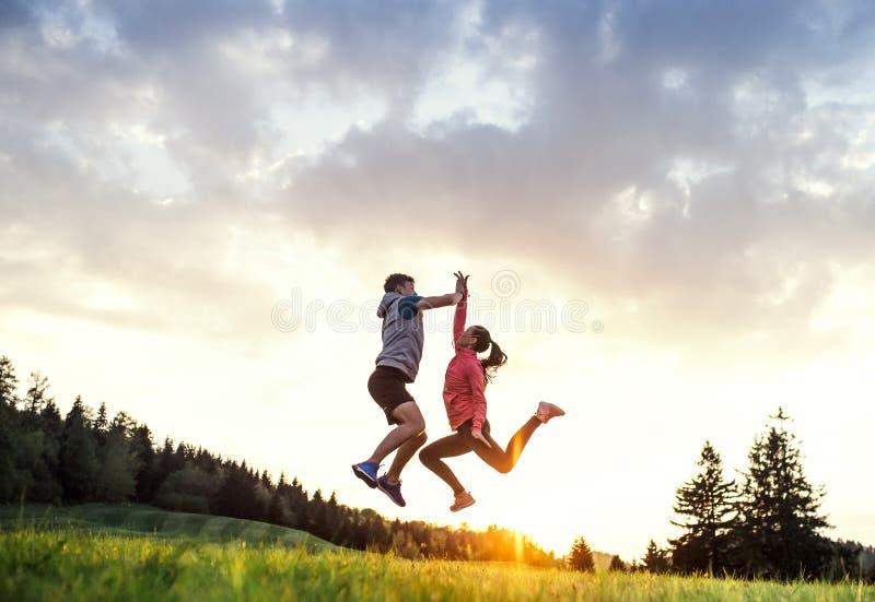 Pares jovenes activos que saltan después de hacer ejercicio en naturaleza en la puesta del sol imagen de archivo libre de regalías