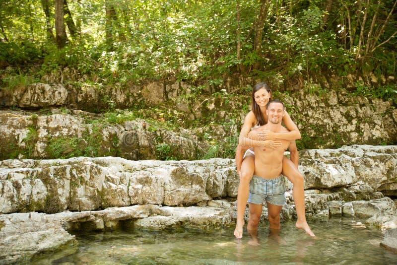 Pares jovenes activos que se enfrían hacia fuera en el río en un día de verano caliente s fotos de archivo libres de regalías