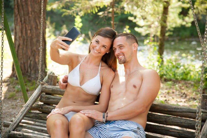 Pares jovenes activos que toman el selfie en un banco en parque cerca del río foto de archivo