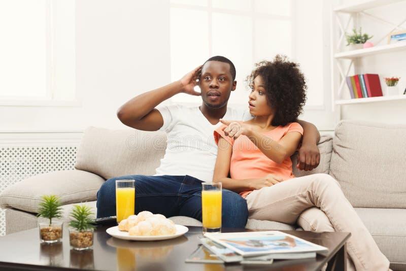 Pares jovenes afroamericanos sorprendidos que ven la TV en casa foto de archivo