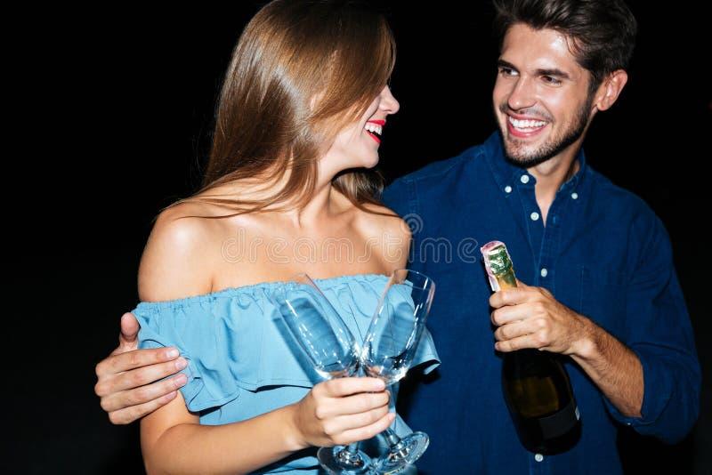 Pares jovenes alegres con los vidrios y la botella de champán fotografía de archivo libre de regalías