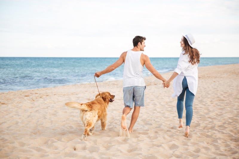 Pares jovenes alegres felices que corren en la playa con su perro foto de archivo
