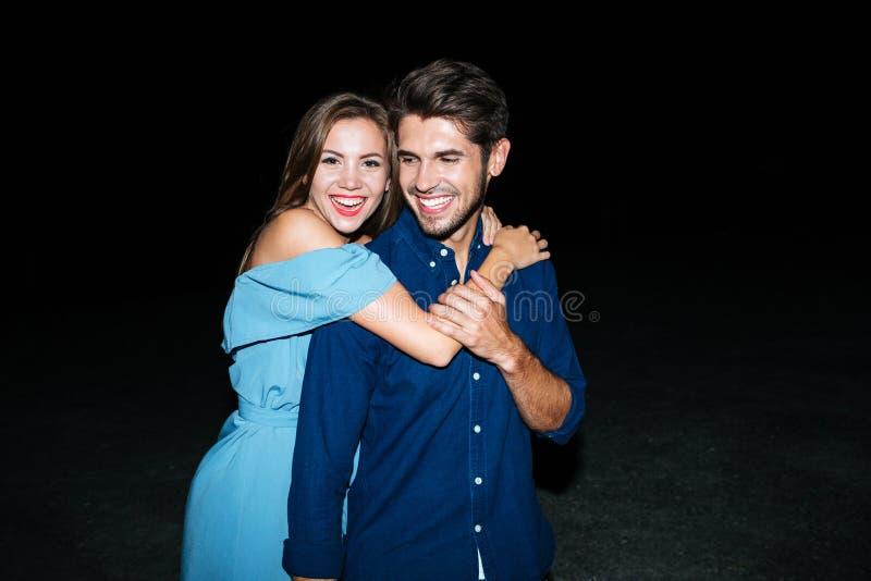 Pares jovenes alegres que abrazan en la playa en la noche foto de archivo libre de regalías