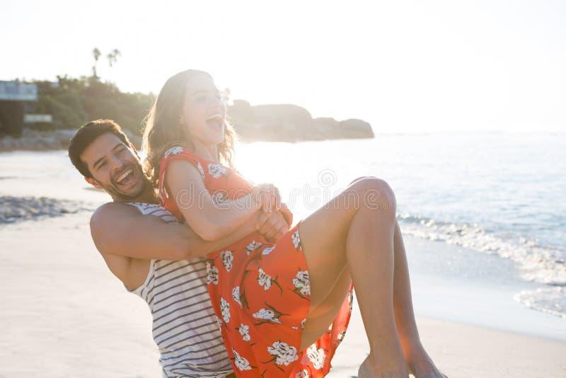 Pares jovenes alegres que gozan en la playa fotos de archivo