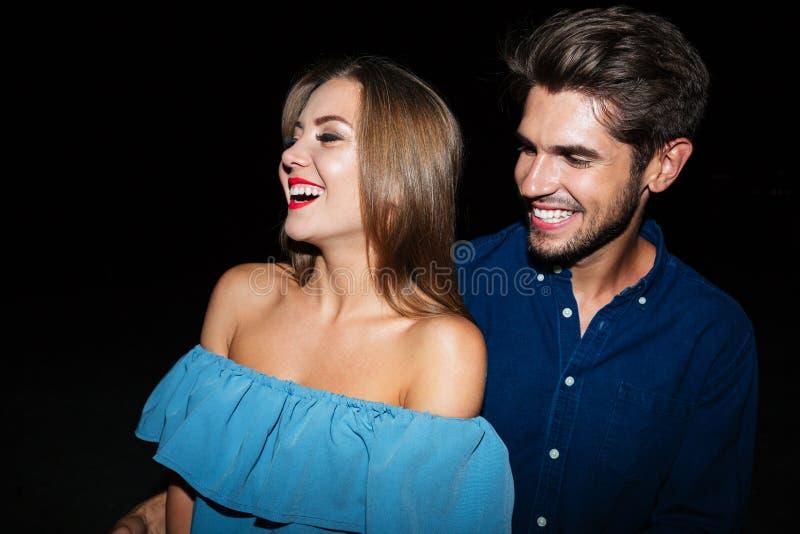 Pares jovenes alegres que ríen junto de la noche imagen de archivo libre de regalías