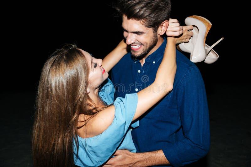 Pares jovenes alegres que se colocan y que abrazan en la noche foto de archivo