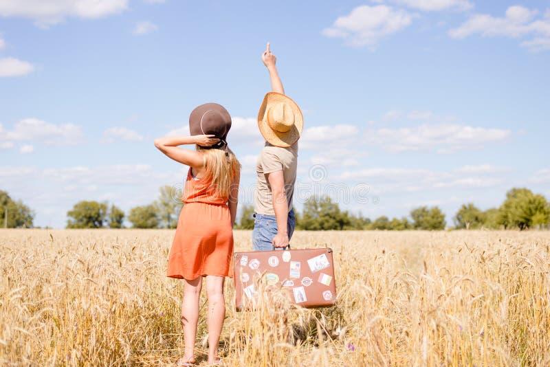 Pares jovenes alegres que se divierten en campo de trigo Hombre emocionado y mujer que señalan en el cielo azul al aire libre fotos de archivo