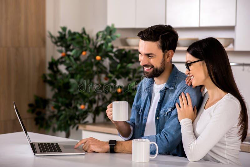 Pares jovenes alegres que se sientan en la cocina imagen de archivo libre de regalías