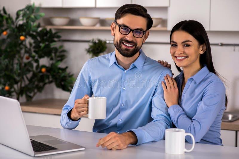 Pares jovenes alegres que se sientan en la cocina foto de archivo