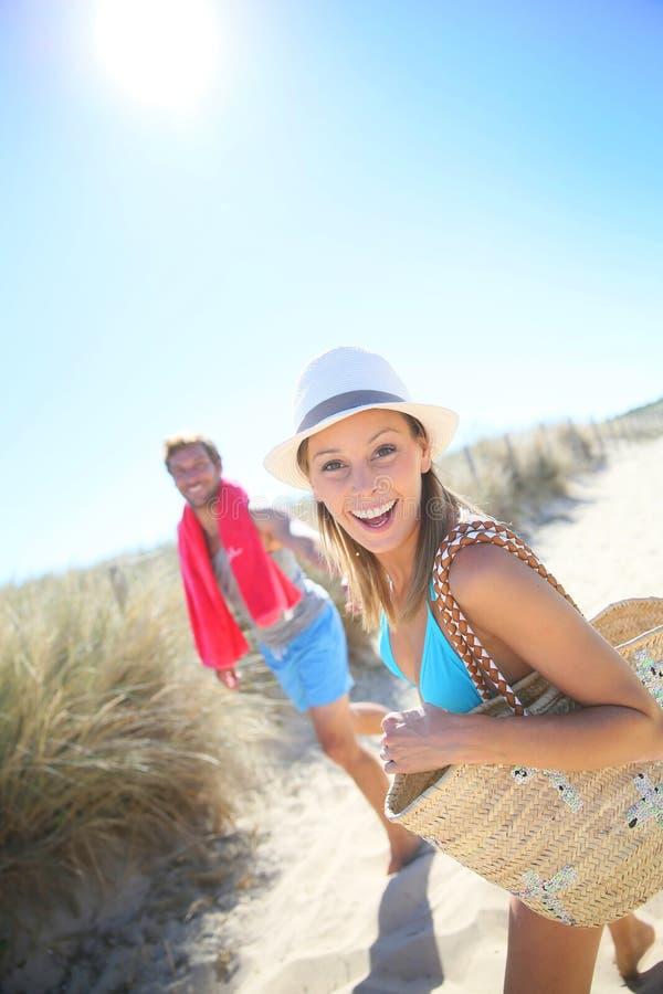 Pares jovenes alegres que van a la playa imagen de archivo