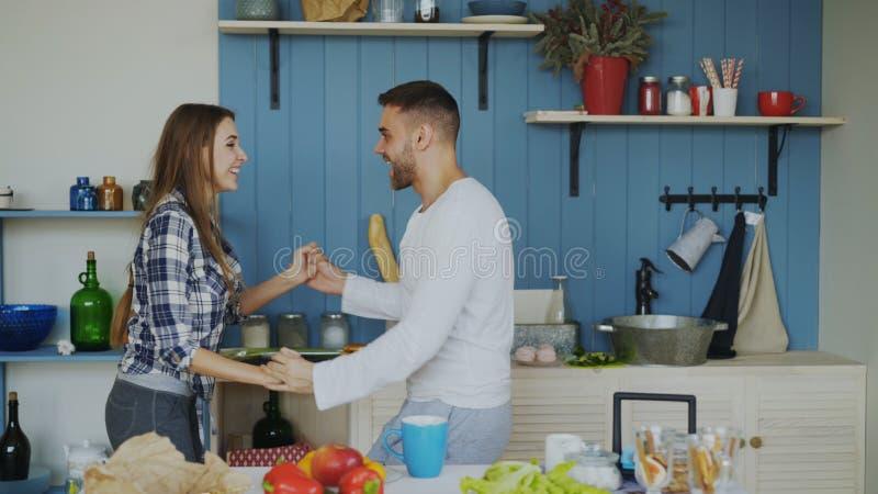 Pares jovenes alegres y atractivos en el amor que baila junto la danza latina en la cocina en casa el días de fiesta foto de archivo libre de regalías