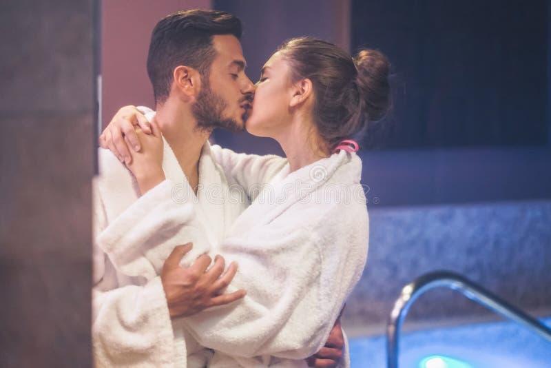 Pares jovenes apasionados que se besan durante un día de centro del balneario de la piscina - amantes románticos que tienen un mo fotografía de archivo