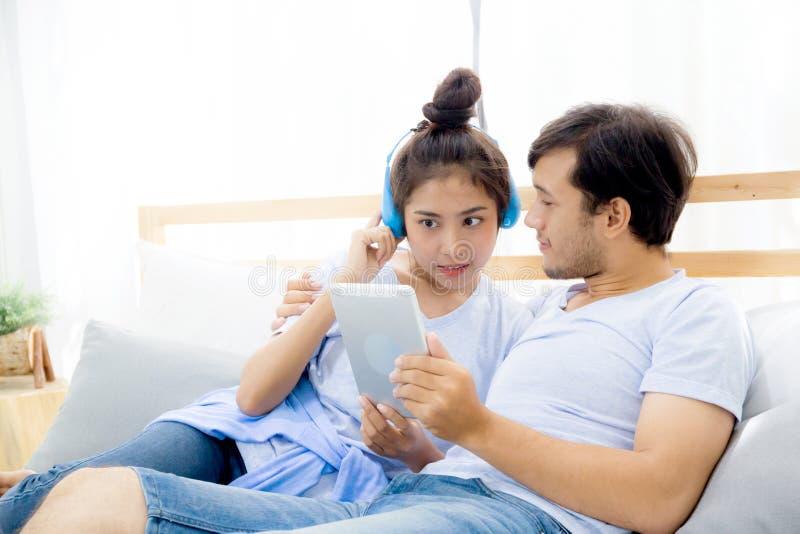 Pares jovenes asiáticos hermosos que escuchan la música con la tableta en cama, amor, fechando fotos de archivo libres de regalías