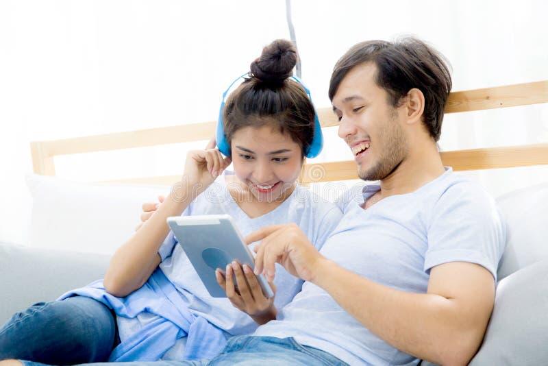Pares jovenes asiáticos hermosos que escuchan la música con la tableta en cama, amor, fechando imagen de archivo libre de regalías