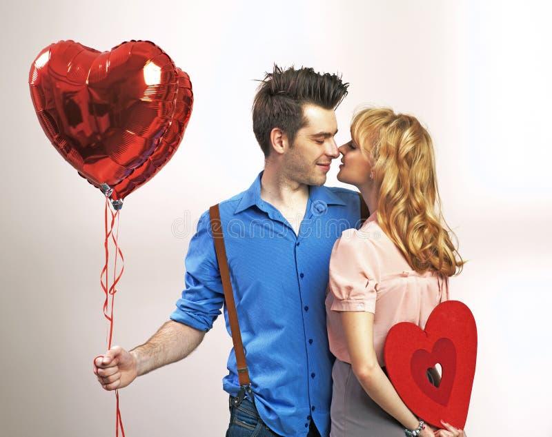 Pares jovenes atractivos durante el día de tarjeta del día de San Valentín