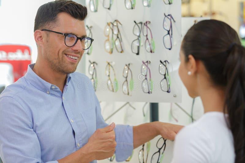 Pares jovenes atractivos en tienda ?ptica imagenes de archivo