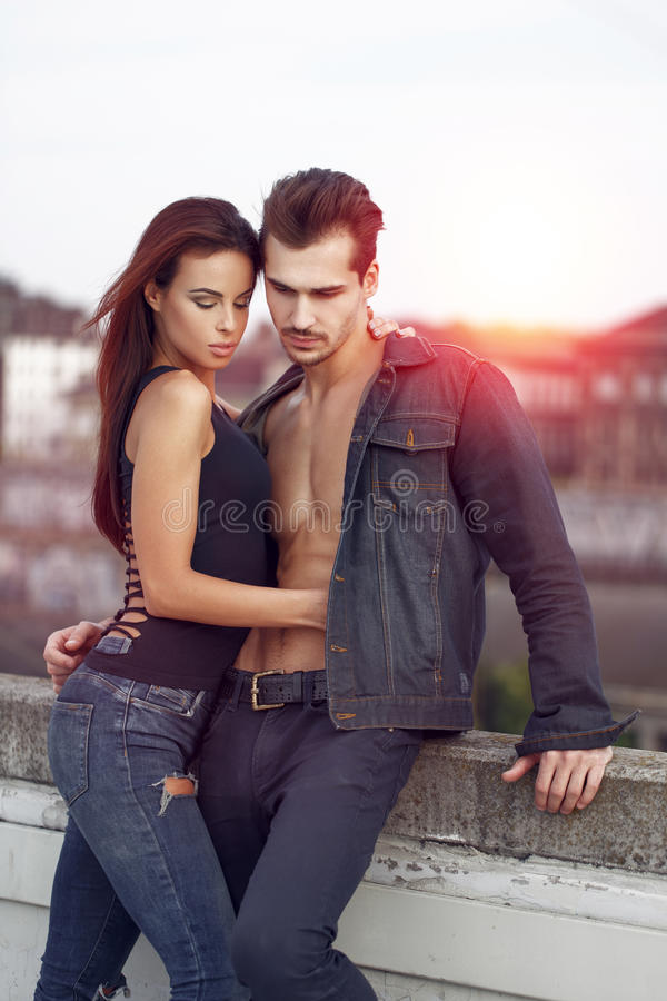 Pares jovenes atractivos que presentan en puesta del sol imagen de archivo
