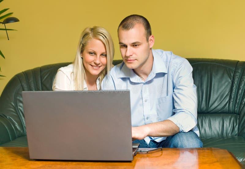 Pares jovenes atractivos usando la computadora portátil. imágenes de archivo libres de regalías