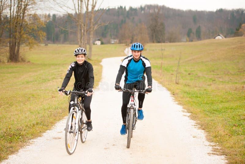 Pares jovenes biking en una tarde del otoño en naturaleza fotos de archivo