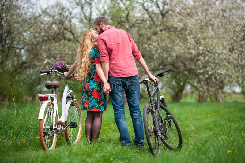 Pares jovenes cariñosos con las bicicletas imágenes de archivo libres de regalías