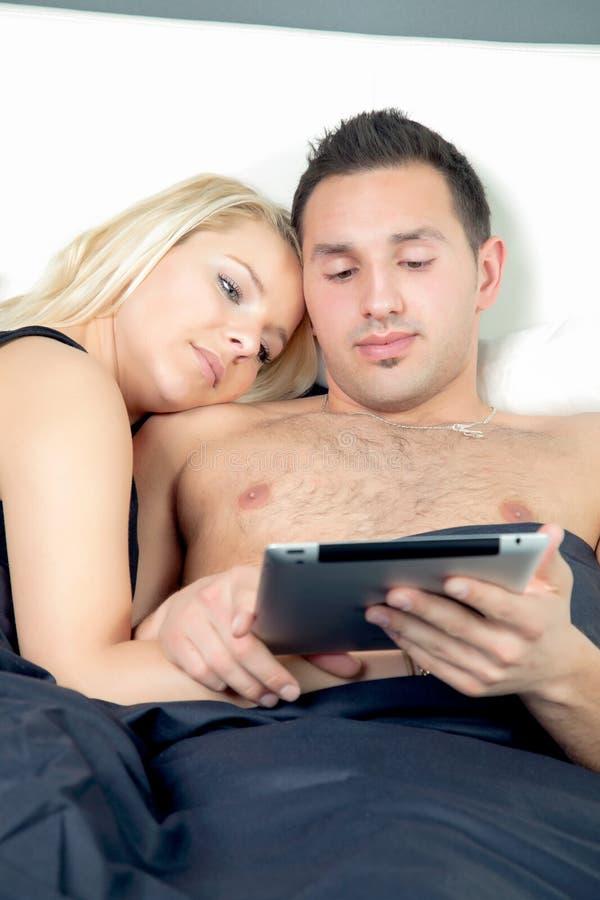 Pares jovenes cariñosos en cama foto de archivo libre de regalías