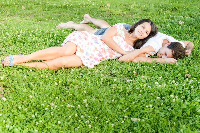 Pares jovenes cariñosos felices al aire libre que se relajan imagen de archivo