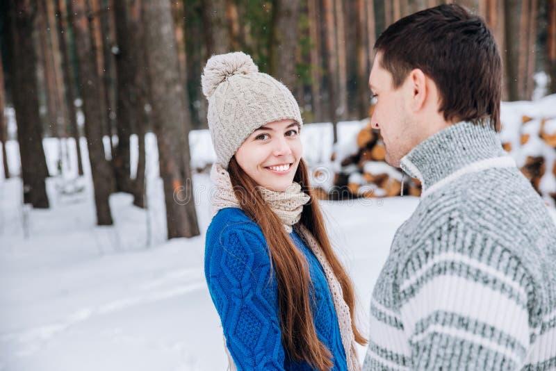 Pares jovenes cariñosos felices que caminan en bosque nevoso del invierno imagenes de archivo