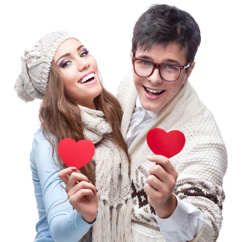 Pares jovenes casuales alegres que llevan a cabo corazones rojos imagen de archivo