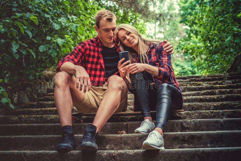 Pares jovenes casuales que se relajan en las escaleras fotografía de archivo