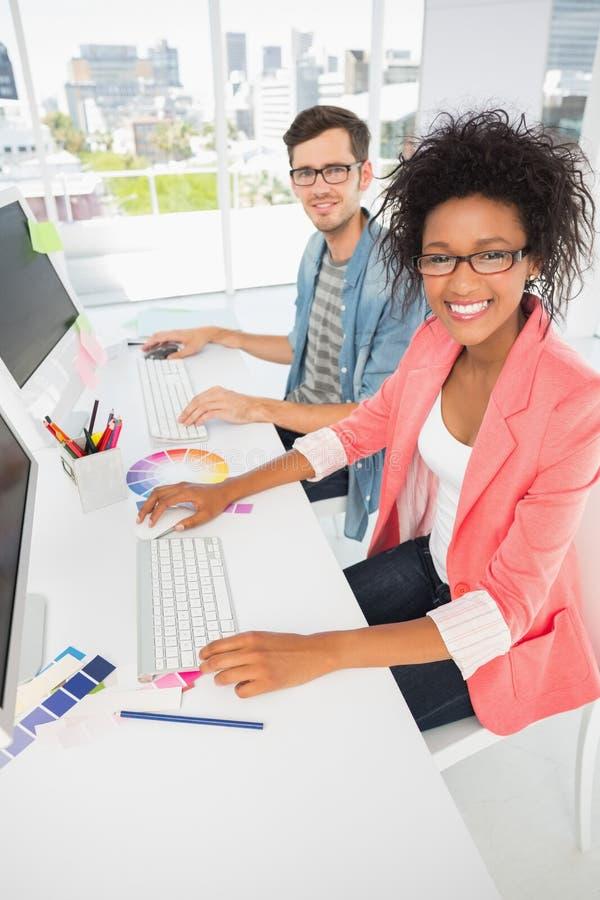 Pares jovenes casuales sonrientes que trabajan en los ordenadores fotos de archivo libres de regalías