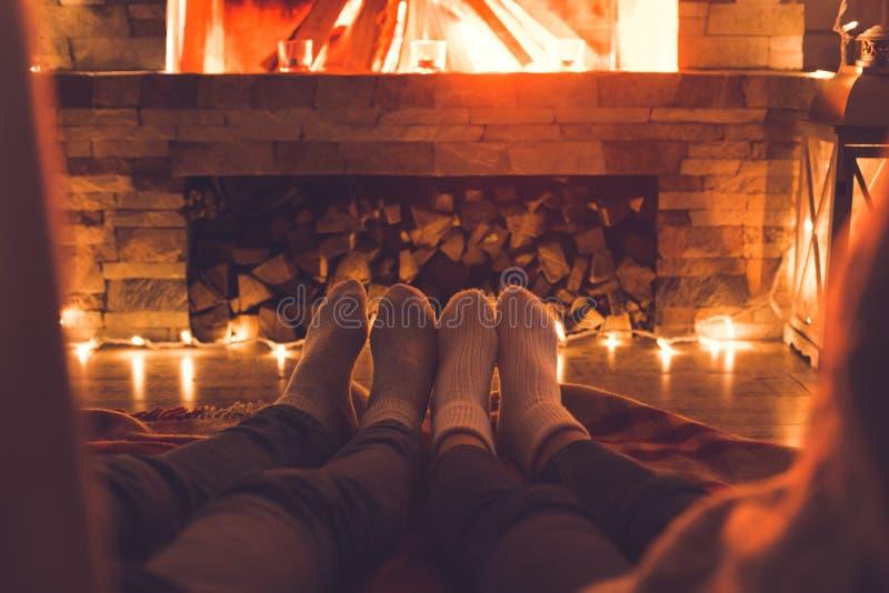 Pares jovenes cerca del primer de las piernas del invierno de la chimenea en casa imagenes de archivo