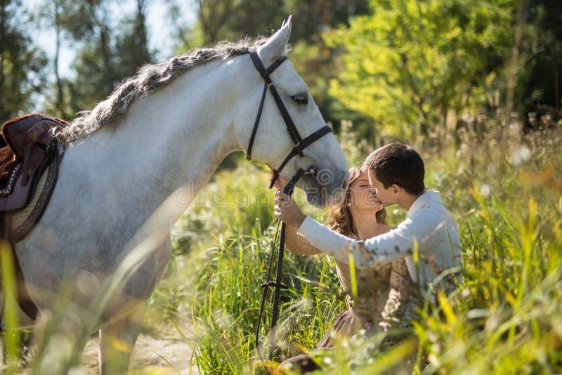 Pares jovenes con el caballo imagen de archivo