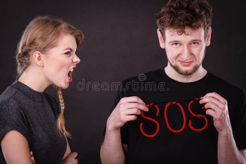 Pares jovenes con el corazón quebrado y la palabra el SOS fotografía de archivo