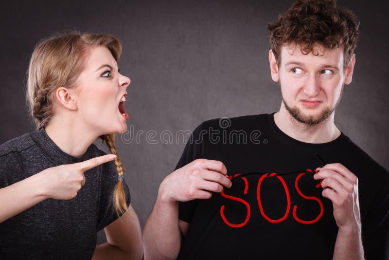 Pares jovenes con el corazón quebrado y la palabra el SOS imagen de archivo libre de regalías