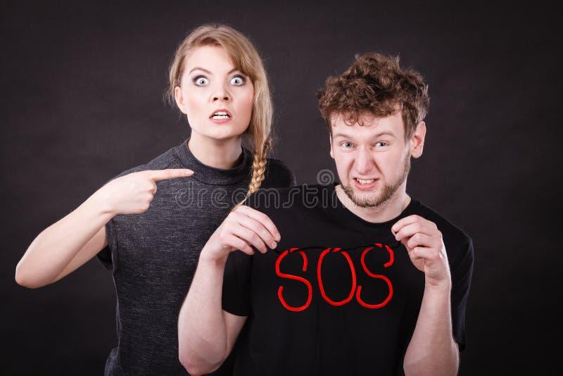 Pares jovenes con el corazón quebrado y la palabra el SOS fotos de archivo