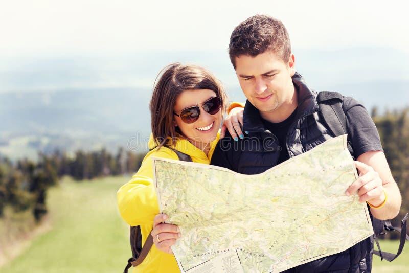 Pares jovenes con el mapa en montañas imagen de archivo libre de regalías