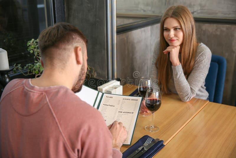 Pares jovenes con el menú que se sienta en restaurante imagen de archivo