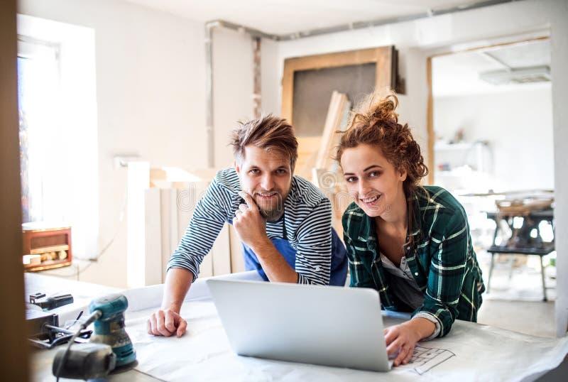 Pares jovenes con el ordenador portátil en el taller del carpintero imagenes de archivo
